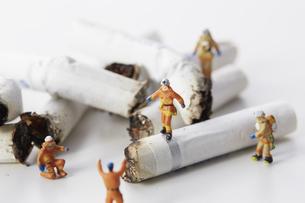 たばこの吸い殻とミニチュアの消防士の写真素材 [FYI04313295]