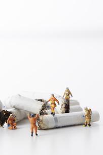 たばこの吸い殻とミニチュアの消防士の写真素材 [FYI04313296]