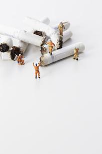 たばこの吸い殻とミニチュアの消防士の写真素材 [FYI04313297]