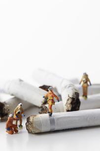 たばこの吸い殻とミニチュアの消防士の写真素材 [FYI04313298]
