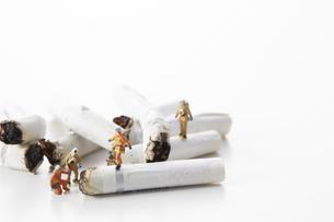 たばこの吸い殻とミニチュアの消防士の写真素材 [FYI04313299]