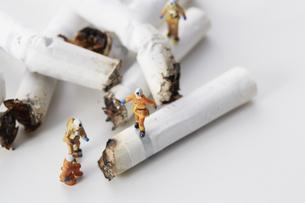たばこの吸い殻とミニチュアの消防士の写真素材 [FYI04313300]