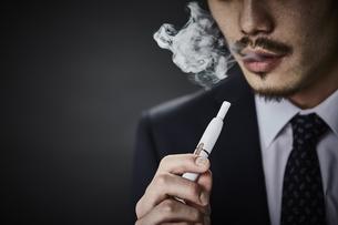 電子タバコを吸う男性の写真素材 [FYI04313315]