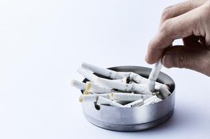 煙草を灰皿に捨てる男性の手の写真素材 [FYI04313318]