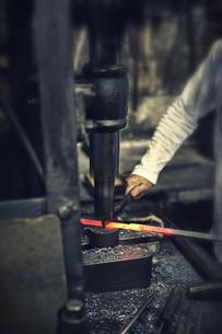 刃物工場で熱され赤くなった鉄を持ち作業する男性の写真素材 [FYI04313320]