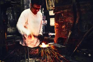 刃物工場で火花を散らしながら作業をする男性の写真素材 [FYI04313321]