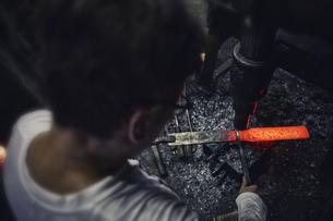 刃物工場で熱され赤くなった鉄を持ち作業する男性の写真素材 [FYI04313325]