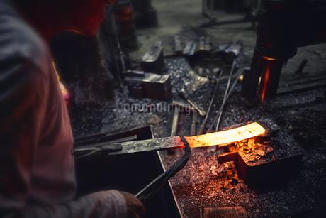 刃物工場で熱され赤くなった鉄を持ち作業する男性の写真素材 [FYI04313326]