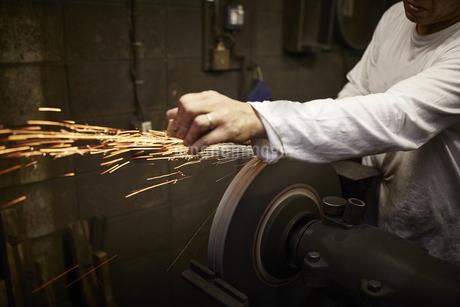 刃物工場で火花を散らしながら作業をする男性の写真素材 [FYI04313329]