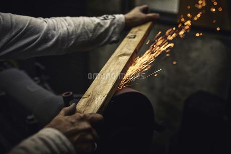 刃物工場で火花を散らしながら作業をする男性の写真素材 [FYI04313330]