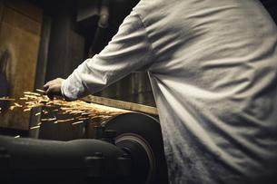 刃物工場で火花を散らしながら作業をする男性の写真素材 [FYI04313331]