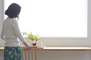 カフェのカウンターの席に座ろうとしている女性の写真素材 [FYI04313385]
