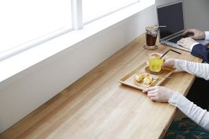カフェのカウンターに座る男性と女性の手元の写真素材 [FYI04313405]
