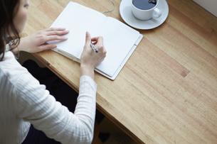 カフェのカウンターで手帳に書き込む女性の写真素材 [FYI04313412]