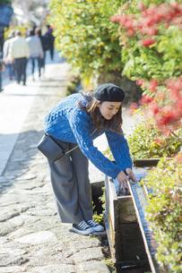 観光地を散策中に湧き水で手を洗う女性の写真素材 [FYI04313684]