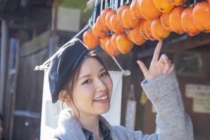 干し柿を指さす女性の写真素材 [FYI04313706]