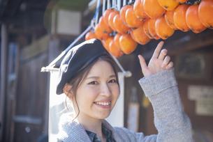 干し柿を指さす女性の写真素材 [FYI04313708]