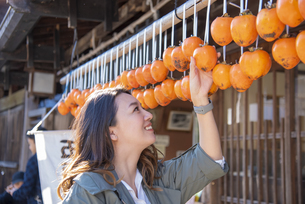 干し柿を指さす女性の写真素材 [FYI04313709]