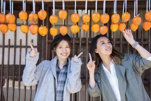 干し柿を指さす女性2人の写真素材 [FYI04313714]