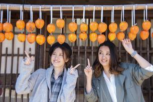 干し柿を指さす女性2人の写真素材 [FYI04313717]