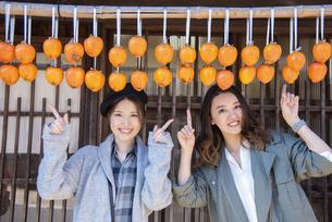 干し柿を指さす女性2人の写真素材 [FYI04313718]