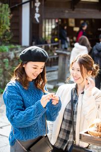 観光地のお店で栗を食べる女性2人の写真素材 [FYI04313802]