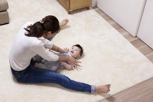 リビングで赤ちゃん体操をしながら笑うお母さんと赤ちゃんの写真素材 [FYI04314217]