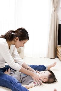 リビングで赤ちゃん体操をしながら笑うお母さんと赤ちゃんの写真素材 [FYI04314218]