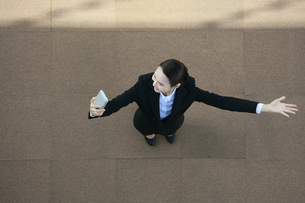 スマートフォンを見ながら腕を広げている女性の写真素材 [FYI04314289]