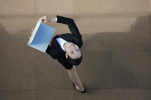 ノートパソコンを持って空を見ているビジネスウーマンの写真素材 [FYI04314307]