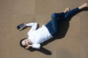 スマートフォンで音楽を聴いている若い女性の写真素材 [FYI04314331]