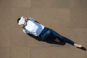 タブレットPCを操作している若い女性の写真素材 [FYI04314339]