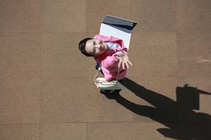 ノートパソコンを操作しながら、手をふっている女性の写真素材 [FYI04314348]