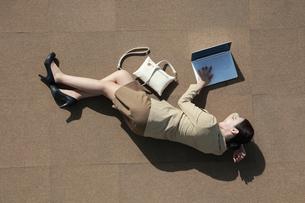 横になってノートパソコンを操作しているビジネスウーマンの写真素材 [FYI04314353]