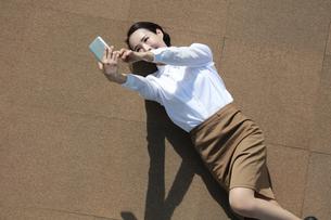 スマートフォンを操作しているビジネスウーマンの写真素材 [FYI04314367]