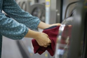 コインランドリーで服を取り出している女性の写真素材 [FYI04314377]