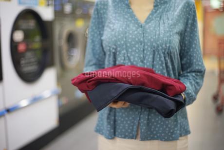 コインランドリーで洗濯物を持っている女性の写真素材 [FYI04314381]
