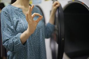 洗濯機の前でオッケーサインをしている女性の写真素材 [FYI04314384]