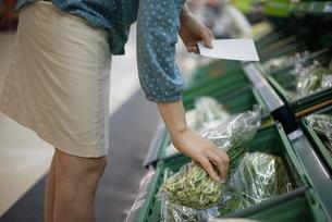 マートでメモ用紙を持って野菜を持っている女性の写真素材 [FYI04314389]