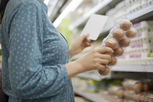 メモ用紙を見ながら卵を持っている女性の写真素材 [FYI04314391]