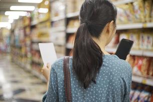 メモ用紙を持って、スマートフォンを見ている女性の写真素材 [FYI04314393]