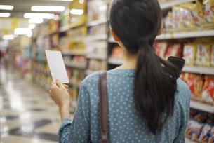 メモ用紙を持って買い物をしている女性の写真素材 [FYI04314394]