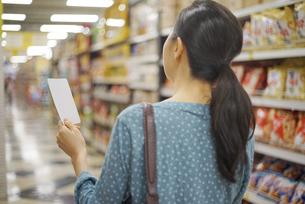 メモ用紙を持って買い物をしている女性の写真素材 [FYI04314395]