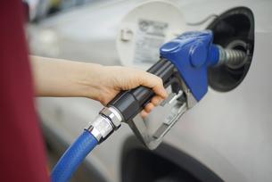 ガソリンスタンドで給油をしている女性の写真素材 [FYI04314396]