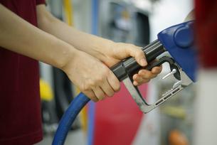 ガソリンスタンドで給油をしている女性の写真素材 [FYI04314398]