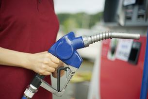 ガソリン給油機を持っている女性の写真素材 [FYI04314401]
