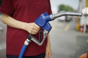 右手でガソリン給油機を持っている女性の写真素材 [FYI04314403]