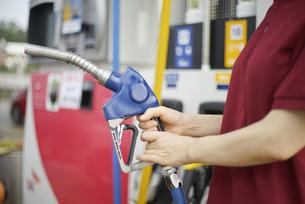 ガソリン給油機を持っている女性の写真素材 [FYI04314409]