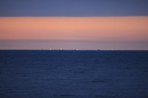 明け方の冬の太平洋と遠くに漁船の明かりの写真素材 [FYI04314505]
