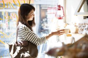 雑貨屋で商品を選んでいる女性の写真素材 [FYI04315429]